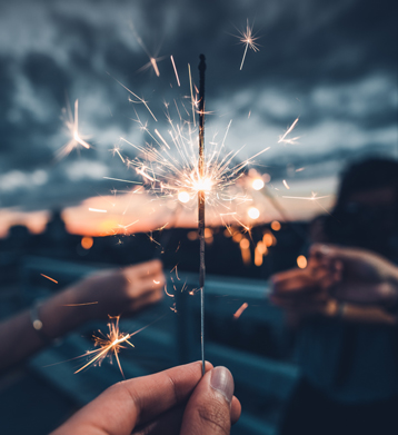 Sparkler held up with sunset in the background