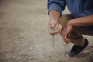 Male hand feeling sand- practicing mindfulness