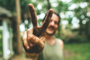 Man holding up a peace sign with his fingers